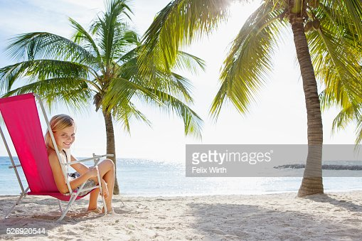 Girl (10-11) relaxing on beach lounger : Stockfoto