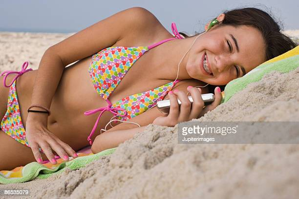 Girl relaxing on beach with media player