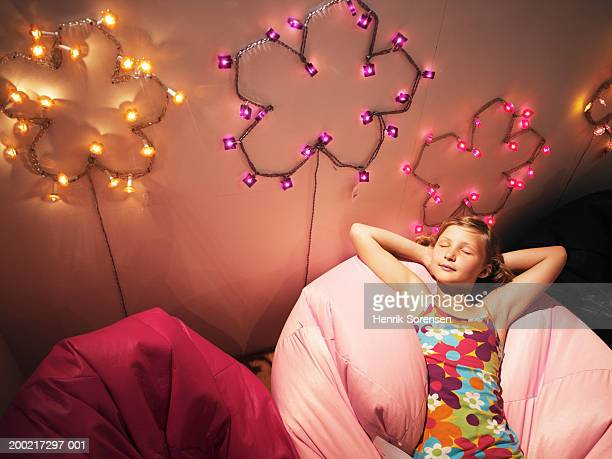 Girl (9-11) relaxing on beanbag, eyes closed, smiling