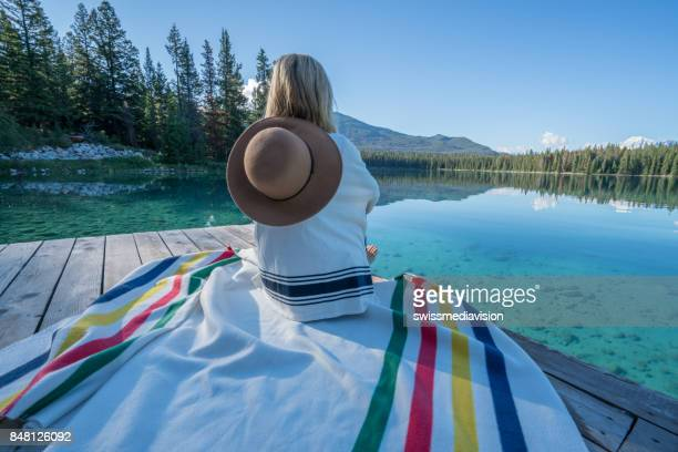 Girl relaxing on lake wooden dock