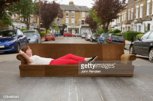 girl relaxing on settee in the street : Stock Photo