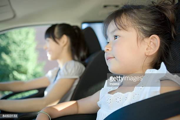 Girl relaxing passenger seat with mother in car