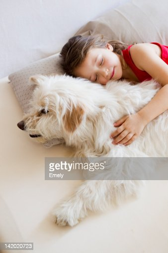Girl relaxing with dog in bed : Stock Photo