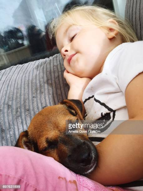 Girl Relaxing With Dog On Sofa At Home