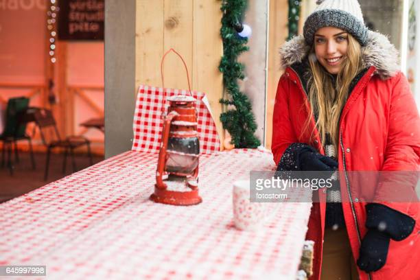 Girl relaxing with hot drink at outdoors winter cafe
