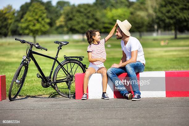 Girl removing father's hat while sitting by bicycle on roadside