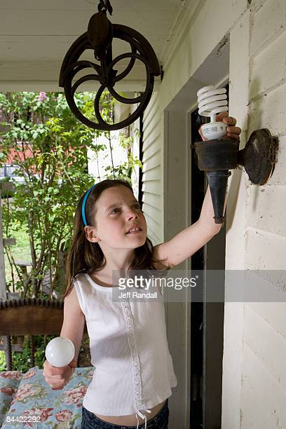Girl replacing energy efficient bulb on porch