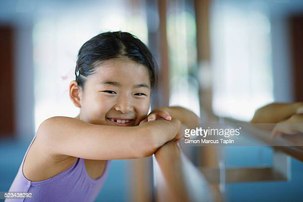 Girl Resting Head on Ballet Bar