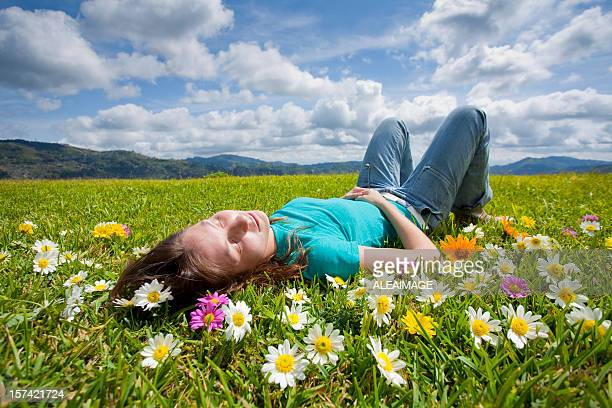 A girl resting in a field of flowers in a meadow