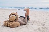 Young woman reading book on a beach. Relaxation travel and vacations concept
