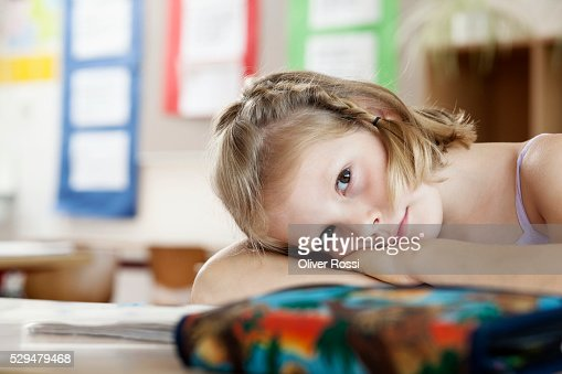 Girl resting on desk in classroom : Stockfoto