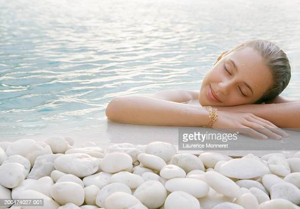 Girl (11-13) resting on edge of swimming pool, dusk