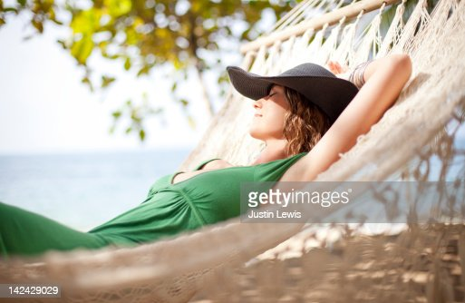 Girl resting on hammock by the beach : Stock Photo