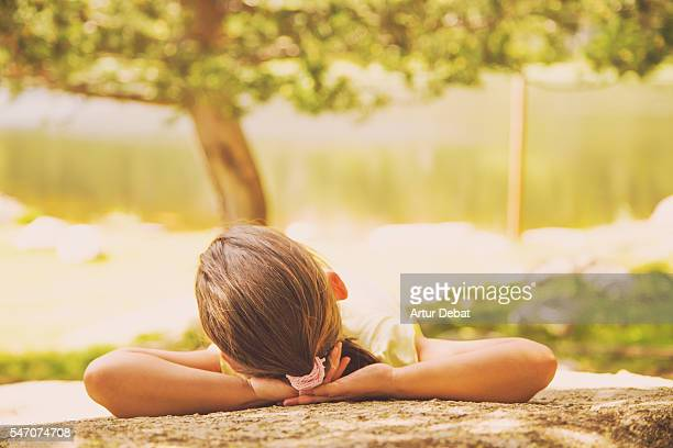 Girl resting on the rock during a family hiking in Catalan Pyrenees mountains during the summer vacations with beautiful views near the lake.