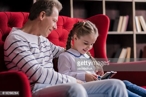 Girl resting with her grandfather and holding the game console : Stock Photo