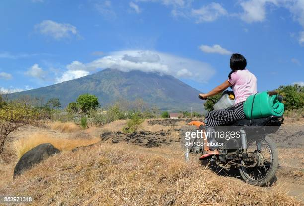 TOPSHOT A girl rides a motorbike in the Kubu subdistrict of Karangasem Regency on the Indonesian resort island of Bali on September 26 as Mount Agung...