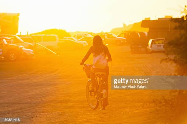 A girl rides her bike during sunset