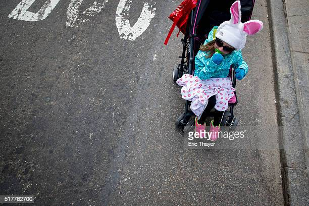 A girl rides in a stroller during the Easter Parade and Bonnet Festival along 5th Avenue March 27 2016 in New York City The parade is a New York...
