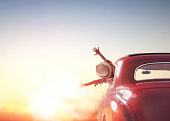 Toward adventure! Girl relaxing and enjoying road trip. Happy girl rides into the sunset in vintage car.
