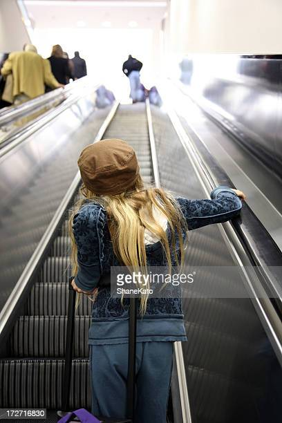Girl rides on escalator in airport