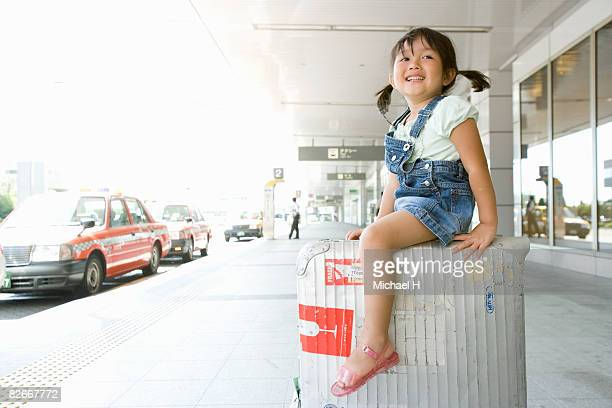 A girl rides suitcase by cabstand in airport