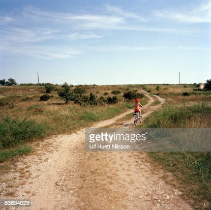 A girl riding a bicycle on a country road Oland Sweden.