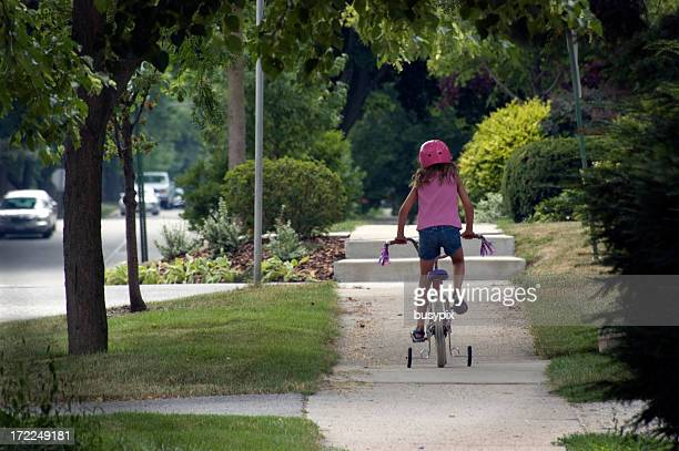 Girl riding a bicycle with training wheels down the sidewalk