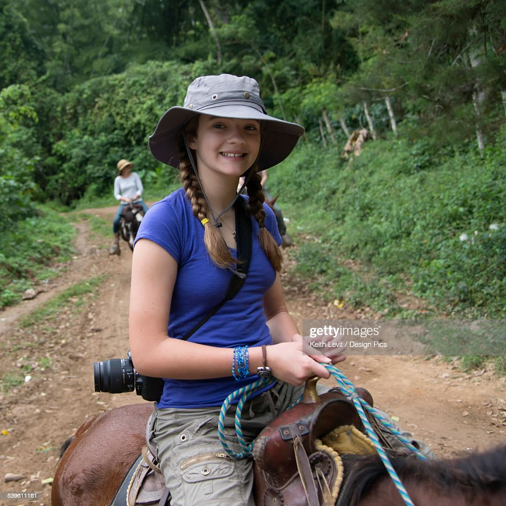 A Girl Riding A Horse On A Trail