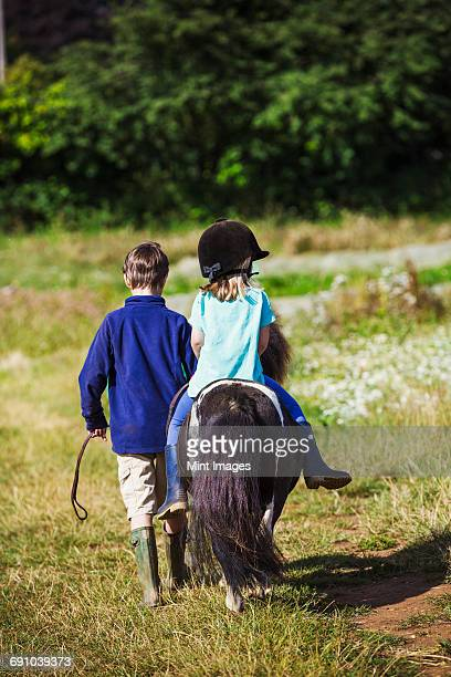 A girl riding a pony and a boy walking through a field.
