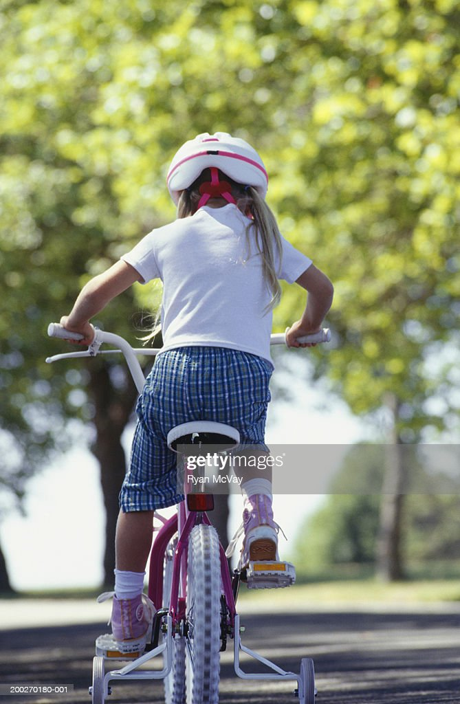 Girl (4-5) riding bicycle in park : Stock Photo