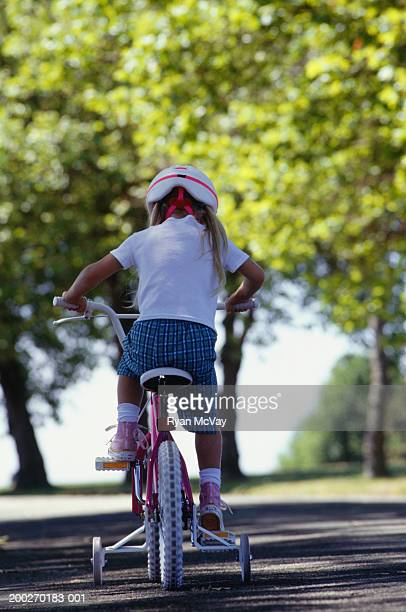 Girl (4-5) riding bicycle in park