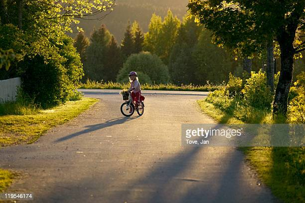 Girl riding bicycle on country road