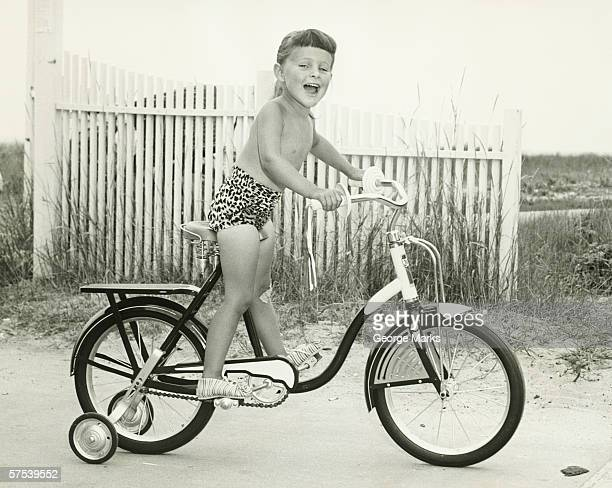 Girl (6-7) riding bicycle with side wheels, (B&W)