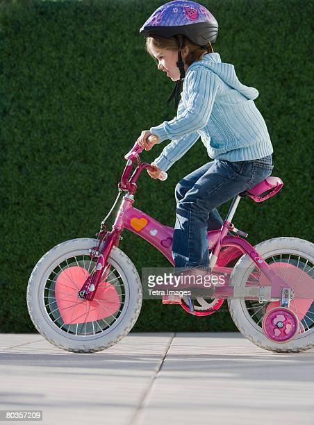 Girl riding bicycle with training wheels