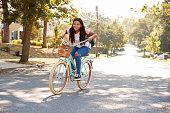 Girl Riding Bike Along Street To School