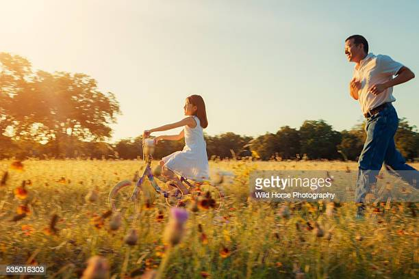 Girl riding bike with father in the field