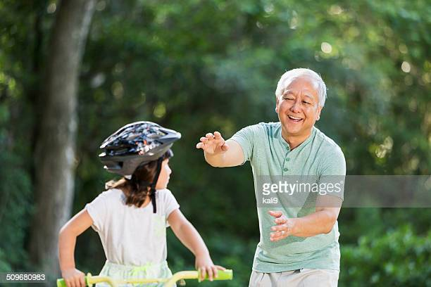 Girl riding bike, with grandfather