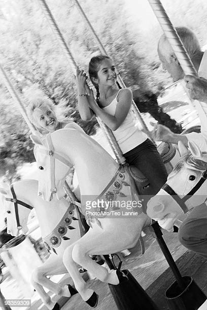 Girl riding carousel with her grandparents