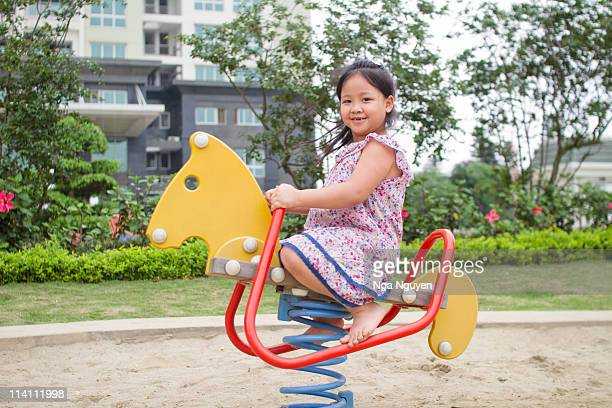 Girl riding horse in playground