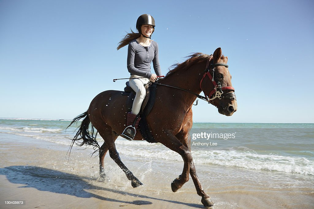 Girl riding horse on beach : Stock Photo