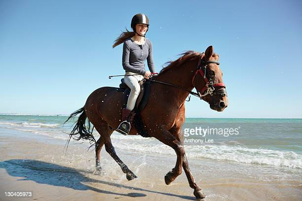 Girl riding horse on beach