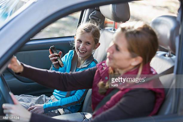 Girl riding in car shows mother her mobile phone