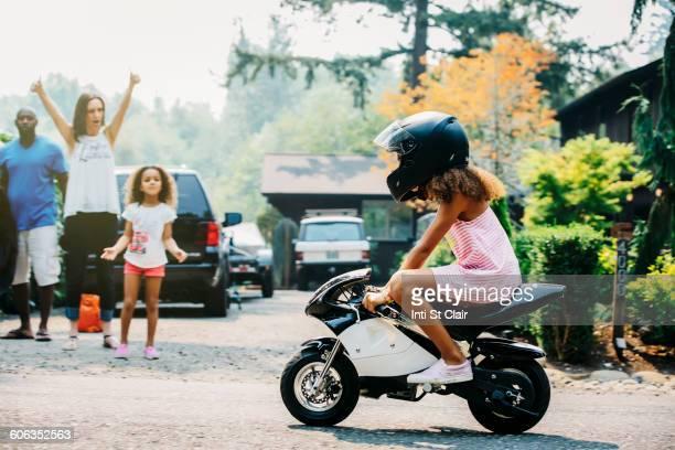 Girl riding miniature motorcycle on street