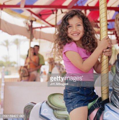 Girl (3-5) riding on carousel, smiling, portrait : Stock Photo