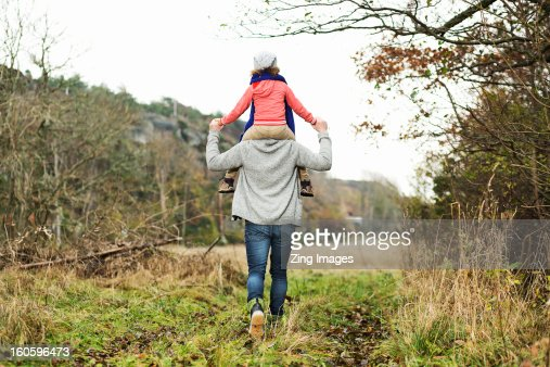 Girl riding on father's shoulders