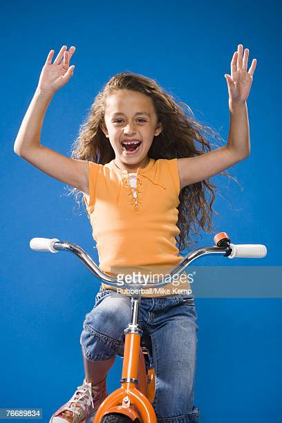 Girl riding orange bicycle with no hands laughing