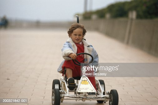 Girl (2-4) riding pedal car outdoors