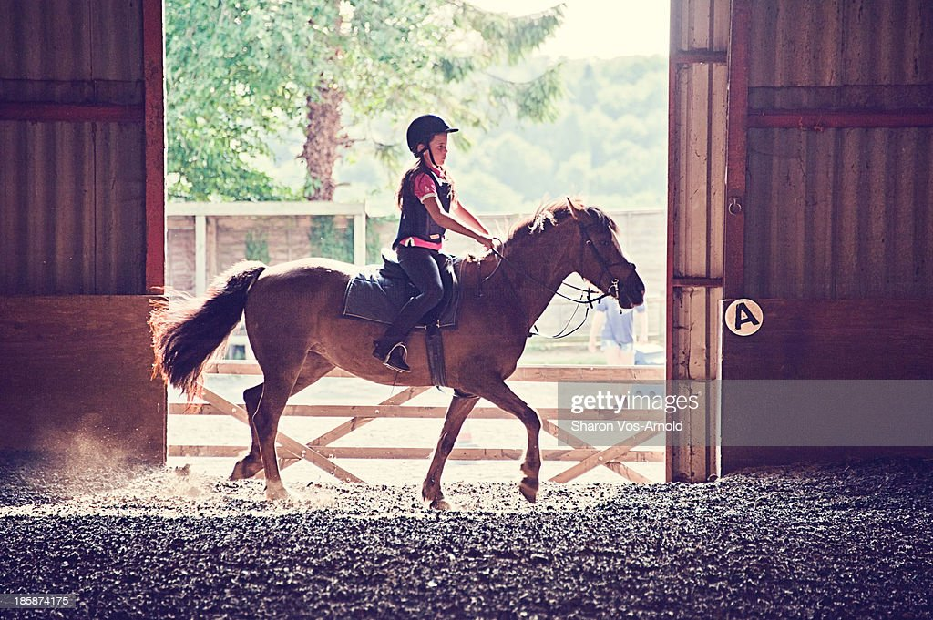 Girl riding pony, indoor school, backlit by sun
