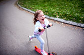 Cute toddler girl riding push scooter in city park