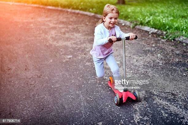 Girl riding push scooter